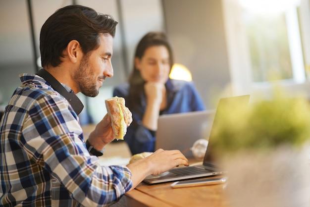 Homme séduisant, manger un sandwich tout en travaillant dans un espace de travail