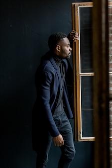 Homme séduisant en manteau sur fond sombre. studio photo professionnel. mode portrait de jeune homme en chemise noire en studio.