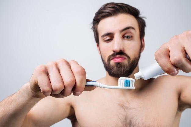 Homme séduisant mettant du dentifrice sur sa brosse à dents. il répète cette routine quotidienne chaque fois qu'il vient aux toilettes le matin et le soir. vue en coupe.