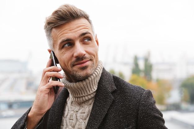 Homme séduisant portant veste marchant à l'extérieur, parlant au téléphone mobile