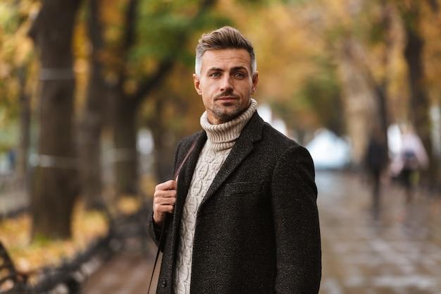 Homme séduisant portant veste marchant à l'extérieur