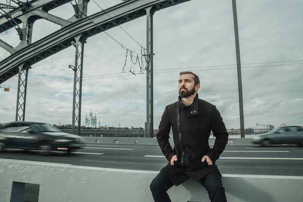 Homme séduisant près de la construction du pont un jour d'automne nuageux
