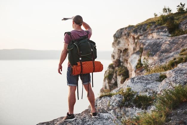 Homme séduisant, profitant de la vue sur le paysage de montagnes au-dessus de la surface de l'eau. concept de vacances d'aventure de style de vie de voyage