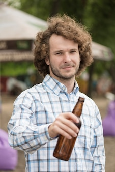 Homme séduisant reposant sur la plage avec de la bière