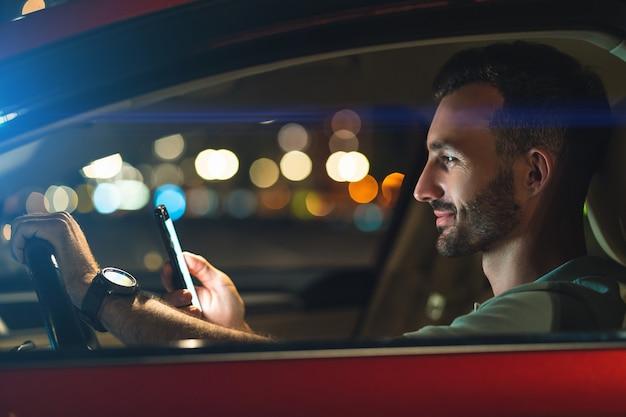 L'homme séduisant avec smartphone assis dans la voiture