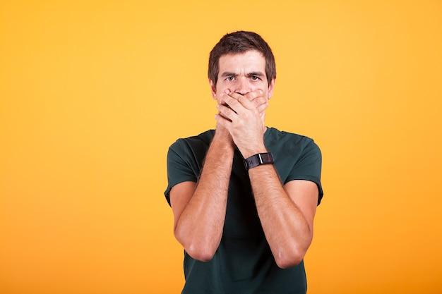 Homme séduisant en t-shirt décontracté couvrant sa bouche en aucun signe de conversation sur fond jaune en photo de studio.