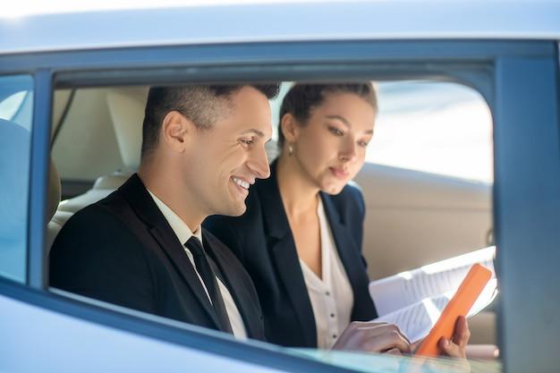 Homme séduisant avec tablette et femme attentive avec des documents en voiture