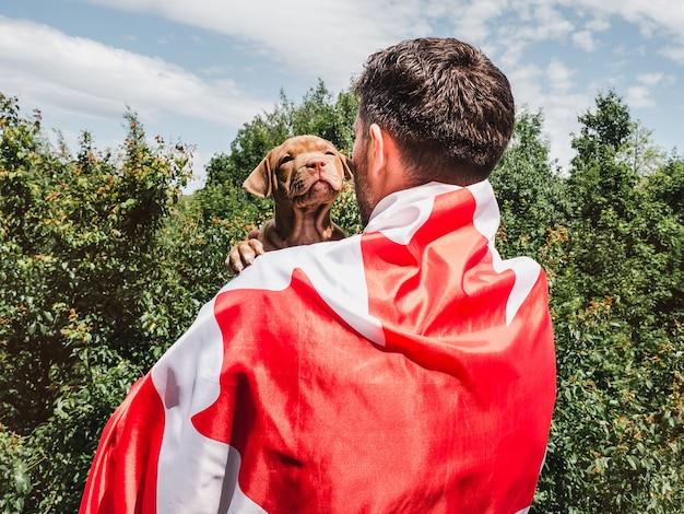 Un homme séduisant tient un charmant chiot sur fond de ciel bleu par une journée claire et ensoleillée. extérieur, gros plan. concept de fête nationale