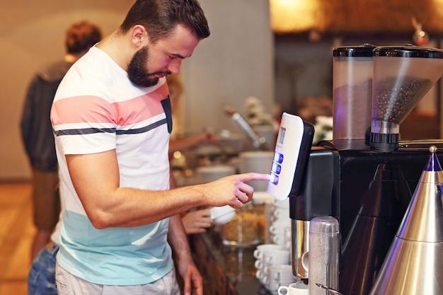 Homme séduisant utilisant une machine à café au buffet du petit-déjeuner à l'hôtel