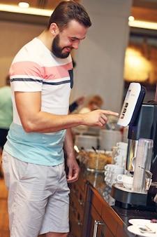 Homme séduisant utilisant une machine à café au buffet du petit-déjeuner