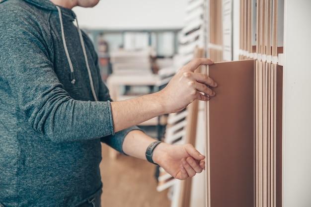Un homme sélectionne le parquet de l'échantillon dans le commerce spécialisé