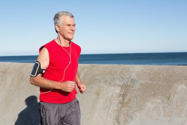 Homme senior actif, faire du jogging sur la jetée