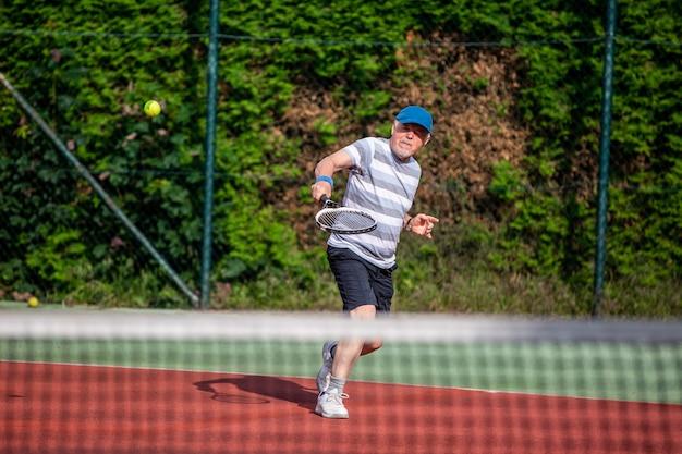 Homme senior actif jouant au tennis en plein air, concept de sport retraité