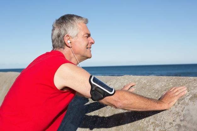 Homme senior actif qui s'étend devant un jogging