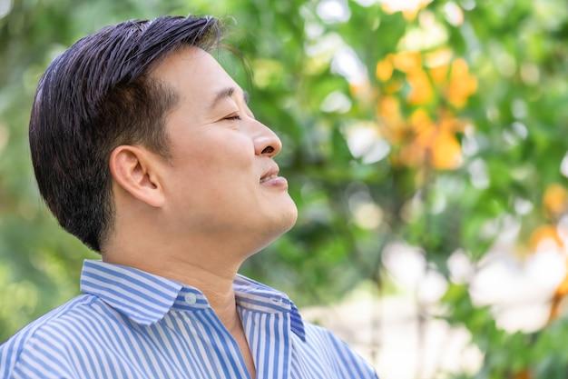 Homme senior asiatique pensant et relaxant dans le parc.