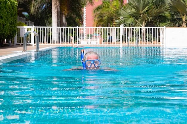 Homme senior aux cheveux blancs nageant dans la piscine extérieure, portant un masque de plongée. retraité heureux et mode de vie sain.