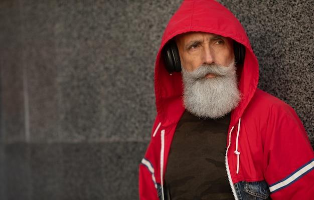 Un homme senior barbu branché, écouter de la musique en plein air. homme mature de mode.