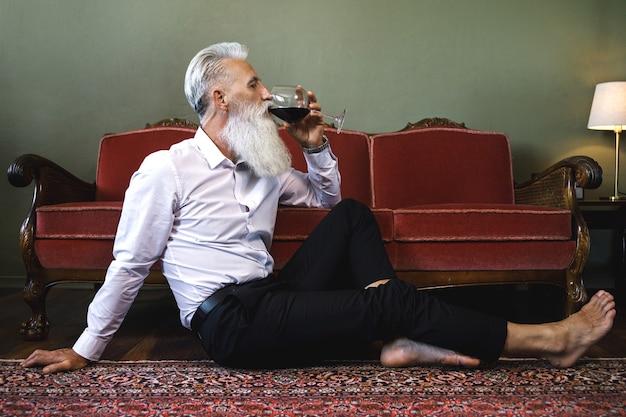 Homme senior barbu élégant et beau assis sur le sol et boire du vin rouge