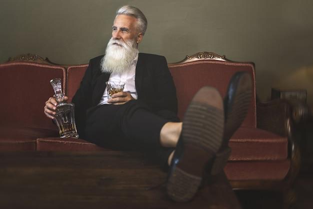 Homme senior barbu élégant et beau buvant du whisky