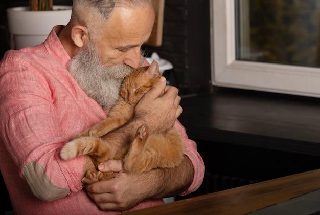 Homme senior barbu tenant un chat mignon à la maison.