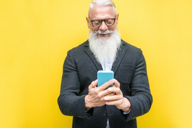 Homme senior branché à l'aide de l'application smartphone sur jaune