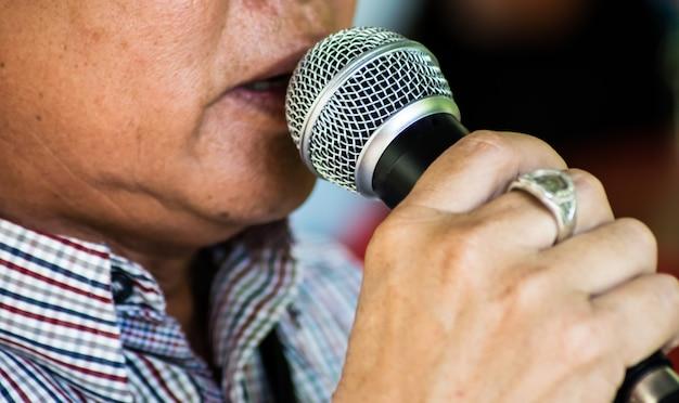 Homme senior chantant avec microphone