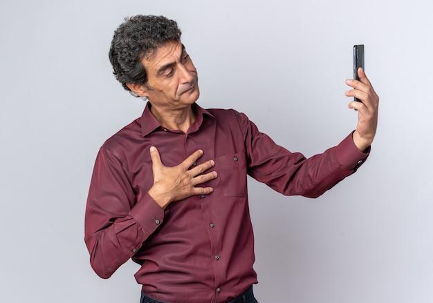 Homme senior en chemise violette faisant selfie à l'aide d'un smartphone à la confiance debout sur blanc