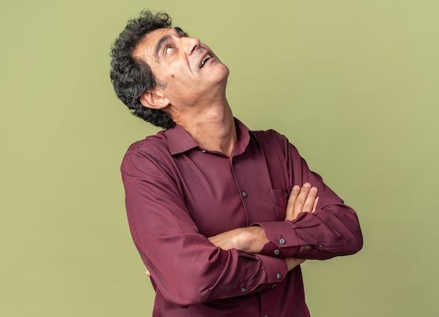 Homme senior en chemise violette jusqu'à intrigué avec les bras croisés debout sur fond vert