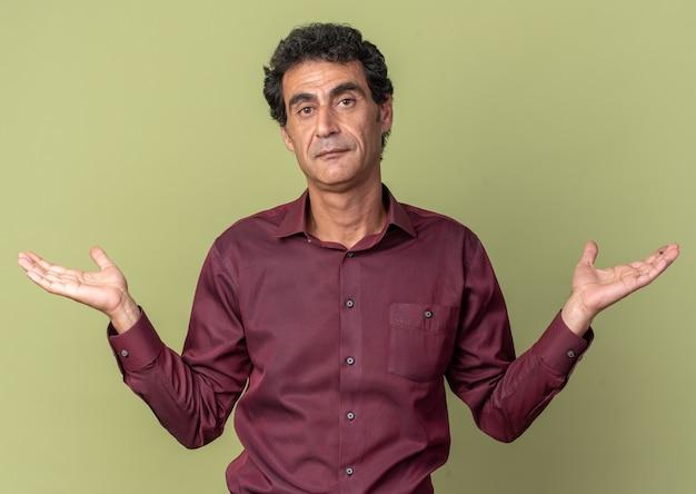 Homme senior en chemise violette regardant la caméra confus écartant les bras sur les côtés n'ayant pas de réponse debout sur fond vert