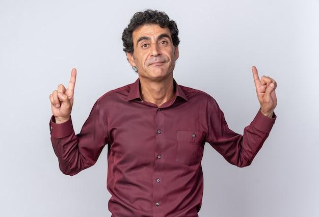 Homme senior en chemise violette regardant la caméra avec une expression sérieuse et confiante pointant avec l'index vers le haut debout sur blanc