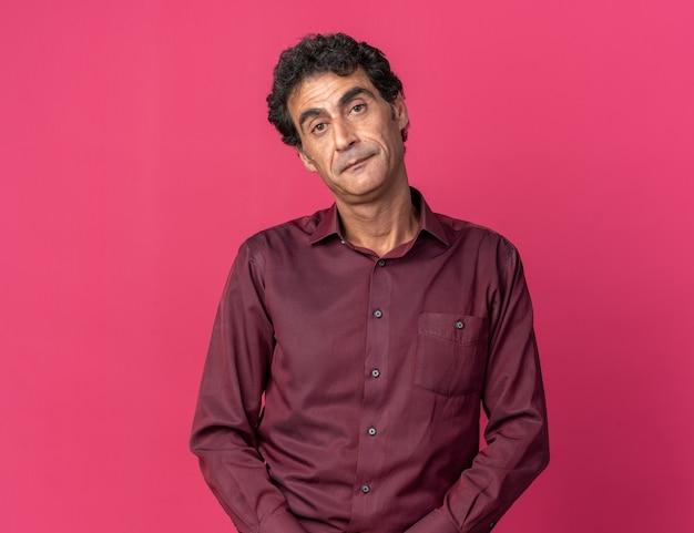Homme senior en chemise violette regardant la caméra avec une expression triste sur le visage debout sur rose