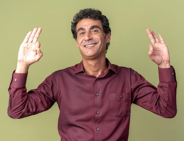 Homme senior en chemise violette regardant la caméra souriant confiant montrant un signe ok debout sur fond vert