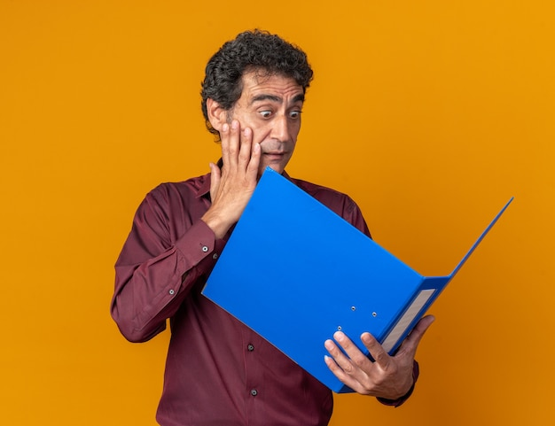 Homme senior en chemise violette tenant un dossier bleu en le regardant étonné et surpris debout sur orange