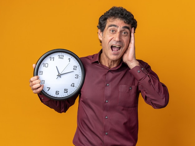 Homme senior en chemise violette tenant une horloge murale regardant la caméra étonné et surpris debout sur fond orange