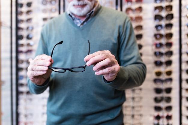 Homme senior choisissant une monture de lunettes dans un magasin d'optique.