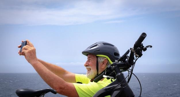 Homme senior ciclyst en excursion en plein air en mer assis sur la falaise à l'aide d'un téléphone portable. retraités joyeux avec casque