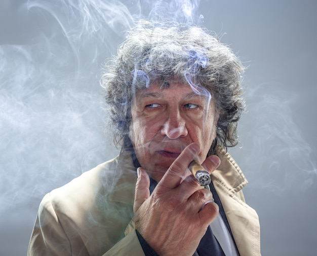 L'homme senior avec cigare comme détective ou patron de la mafia