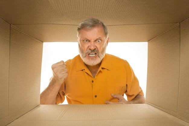 Homme senior en colère ouvrant le plus gros colis postal isolé sur blanc. modèle masculin en colère sur le dessus de la boîte en carton
