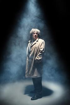 L'homme senior comme détective ou patron de la mafia sur fond gris studio