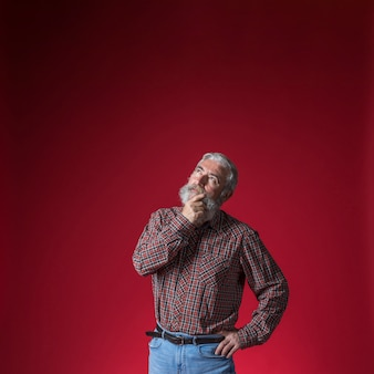 Homme senior contemplé avec la main sur son menton, levant les yeux sur fond rouge