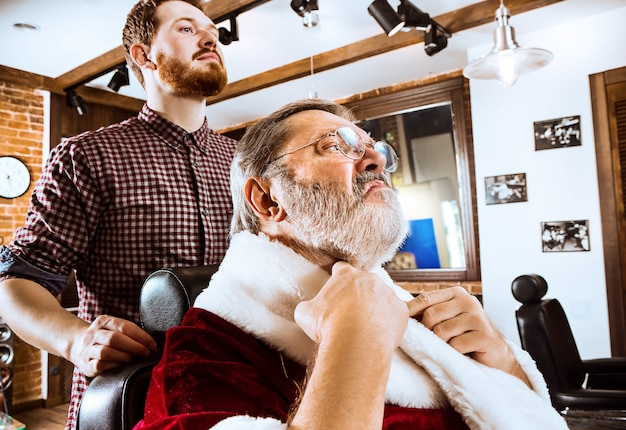 L'homme senior en costume de père noël raser son maître personnel au salon de coiffure avant noël