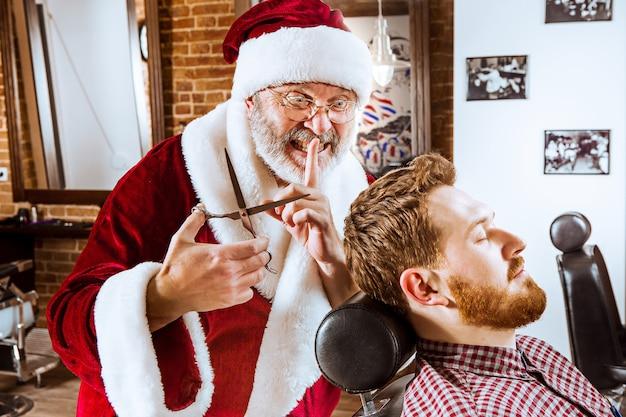 L'homme senior en costume de père noël travaillant comme maître personnel avec des ciseaux au salon de coiffure avant noël