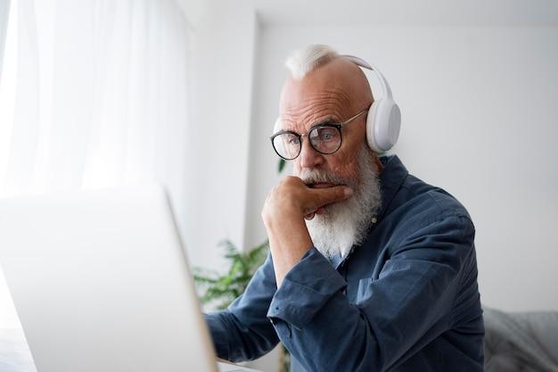 Homme senior de coup moyen portant des écouteurs