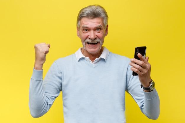 Un homme senior émotionnel avec un téléphone gagne quelque chose en posant sur un mur jaune