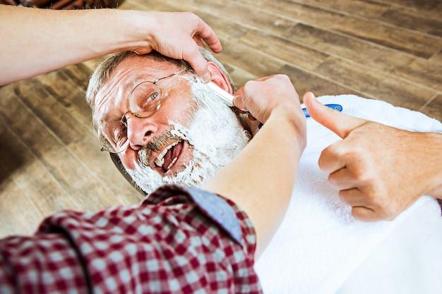 Homme senior émotionnel visite coiffeur en salon de coiffure