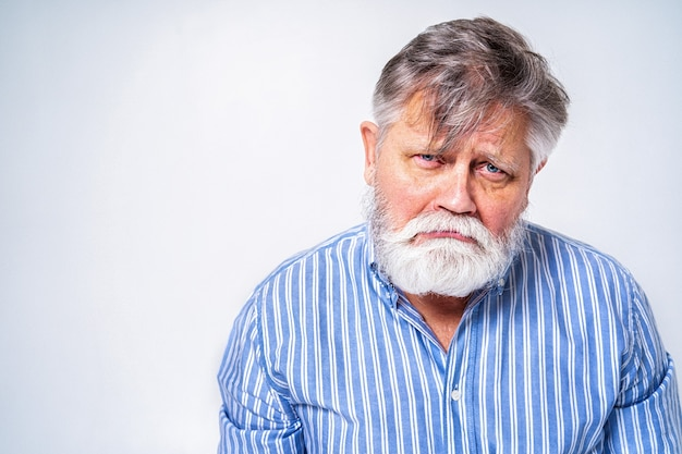 Homme senior excentrique avec portrait d'expression drôle isolé sur blanc