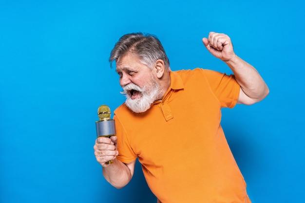 Homme senior excentrique avec portrait d'expression drôle isolé sur bleu