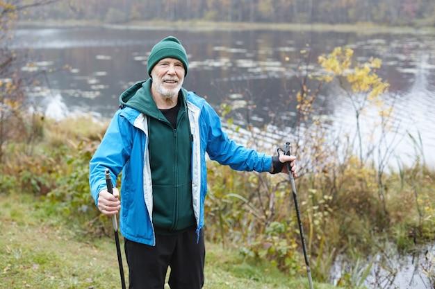 Homme senior expressif posant en plein air