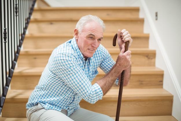 Homme senior fatigué assis sur les escaliers