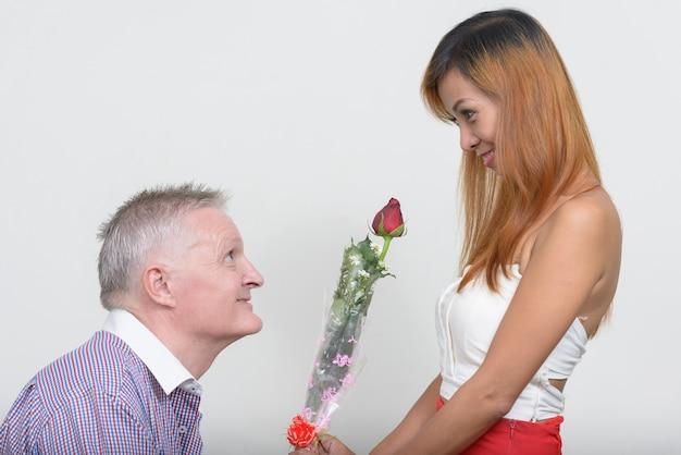 Homme senior et femme asiatique mature en couple ensemble et amoureux contre blanc